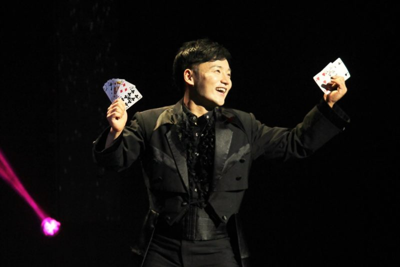 "An Ha Lim, also known as ""The Manipulator"" stands on stage with cards fanned out in both hands, getting ready for his magic trick."